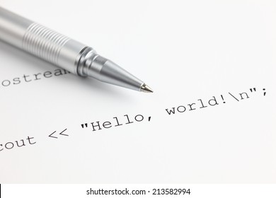 "C++ program code ""Hello, world!"" and ballpoint pen. Closeup."