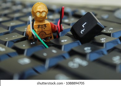 C3PO robot from Star Wars movies fixing Keyboard from computer. Repair job, PC service, online support. Editorial image.