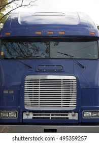 Cab of large blue commercial truck tractor, close up.  Shows grille, windshield, lights and windshield wipers, part of bumper