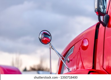 The cab of the red professional industrial grade big rig semi truck standing on the parking lot near warehouse is reflected in the round rear-view mirror attached to the fender of the truck