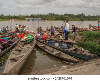 Caballococha, Peru - May 12, 2017:  People on the traditional, indian  boats in the small village Caballococh  on the bank of the river. Amazonia. South America