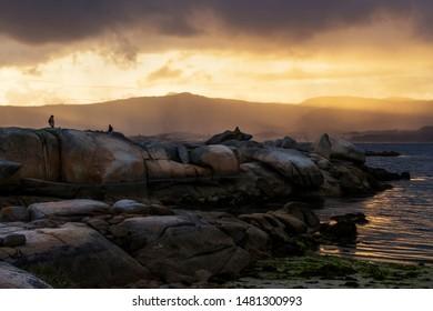 Cabalo Point coastal granite rocks in Arousa Island on stormy sunset wiyh Curota mount at background