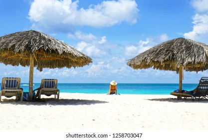 Cabana, parasol. White sand beach. Blue sea water and dramatic clouds. Oranjestad, Aruba. Famous Eagle Beach.  Unidentifiable sun bather.