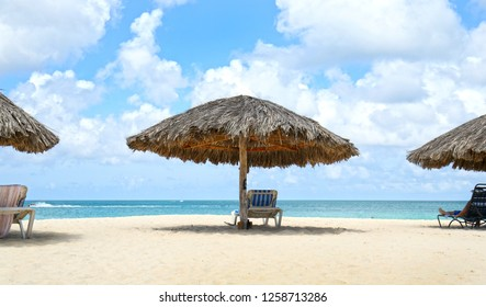 Cabana, parasol. White sand beach. Blue sea water and dramatic clouds. Oranjestad, Aruba. Famous Eagle Beach.