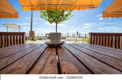 Cabanas de Tavira,  Portugal - October 14th, 2018: Portuguese espresso coffee cup or bica over wooden table. Relaxing at terrace of Cabanas de Tavira, Algarve, Portugal