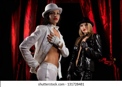 Cabaret performers weared white and black clothes on stage looking at the audience