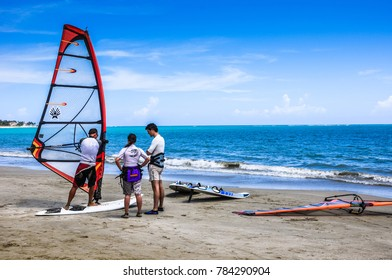 Cabarete / Dominican Republic - July 12, 2011:  young active couple takes a windsurfing lesson with an instructor on ocean shore.