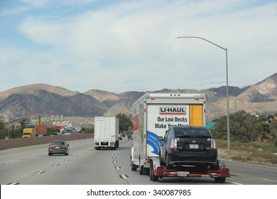 Cabazon, California, USA - October 14, 2015: U-Haul Truck is towing a car on a freeway. U-Haul, an American moving equipment and storage rental company, provides trucks for rental suitable for moving.