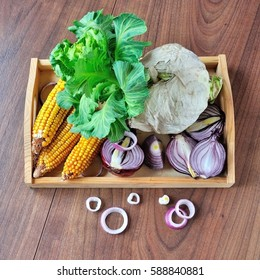 Cabbage, corn and onions on wooden tray.