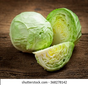 cabbage and cutted cabbage on wooden
