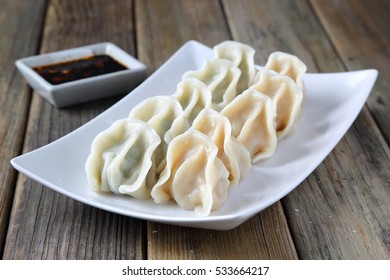 cabbage flavor and chives flavor dumplings on a white plate, with chili, garlic, ginger and soy sauce, wooden table, chop sticks