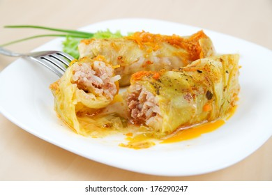 Cabbage rolls on a white plate.