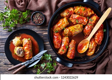 cabbage rolls stuffed with ground beef and rice and cooked to perfection with a tangy tomato sauce in a dutch oven and served on a plate with cutlery, view from above, close-up, flatlay