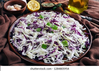 Cabbage Slaw, Malfouf Salad with lemon juice, olive oil, garlic, and mint in an earthenware bowl with brown cloth and ingredients on a rustic table, horizontal view from above, close-up