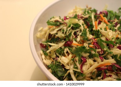Cabbage slaw mix with raw kale, carrots and craisins all in a white salad bowl.
