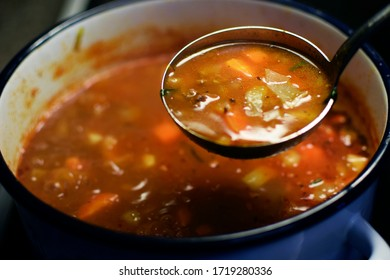 Cabbage soup. Blurred cooking pot on background. Focus in ladle.