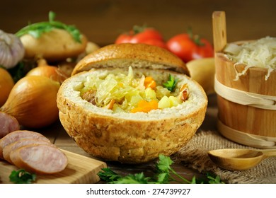 Cabbage soup in a loaf of bread and vegetables on a wooden table