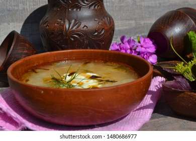 Cabbage soup made from sauerkraut with red pepper. Russian cuisine, ceramic bowls
