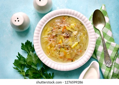 Cabbage soup ( shchi ) with chicken in a white bowl over light blue slate, stone or concrete background.Top view with copy space.