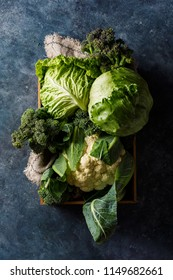 Cabbage in a wooden box, top view. Savoy cabbage, broccoli and iceberg lettuce. Organic vegetables. Top view.
