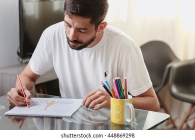 Cabedelo, Paraiba, Brazil - May 24, 2016 - Man at a table with an adult coloring book, new stress relieving trend, mindfulness concept. illustrative editorial.