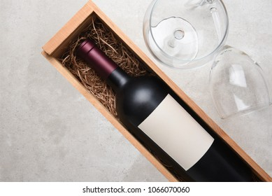 Cabernet Sauvignon: A bottle in wood case with glasses and copy space.