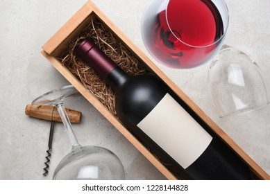 Cabernet Wine Still Life: A bottle in wood case with glasses and corkscrew.