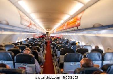 cabin of airplane with passengers on seats waiting to take off.