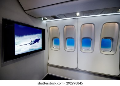 Cabin comfortable flight   passenger plane interior with LCD TV monitor screen display and plane window porthole