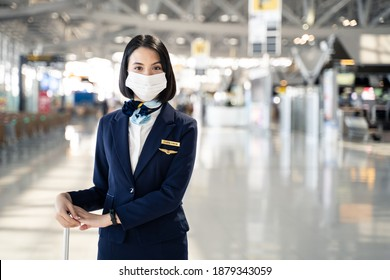 Cabin crew or air hostess wearing face mask walking in airport terminal to the airplanel during the COVID pandemic to prevent coronavirus infection. New normal lifestyle in air transport concept.