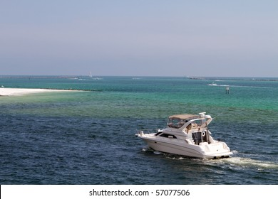 Cabin cruiser motors through the waters of Destin Pass, Florida.