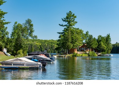 Cabin and docked motorboats on a lake in Ontario Canada's Cottage Country with a blue sky on a summer morning.