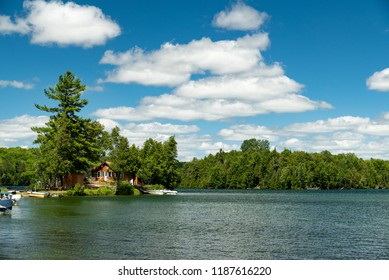 Cabin and docked motorboats on a lake in Ontario Canada's Cottage Country with clouds in a blue sky on a summer afternoon.