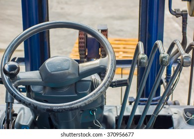 Cabin forklift truck with levers and steering wheel control.