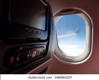 Cabin with LCD monitors with remote control. Passenger plane interior. Fast and comfortable traveling. Monitor as means of getting fun and information.
