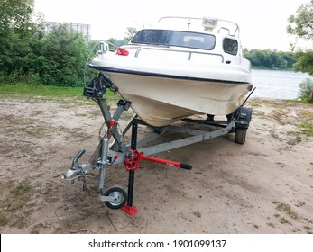 Cabin motor boat on car trailer. Active outdoor recreation, launching a boat - slipping a motor plastic boat on a trailer