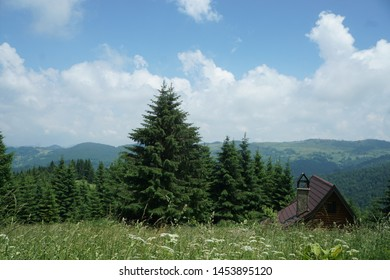 cabin in the mountains. Blue sky. Grass field.