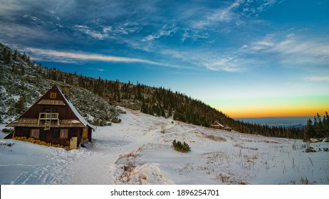 a cabin in the mountains in the light of the setting sun - Shutterstock ID 1896254701