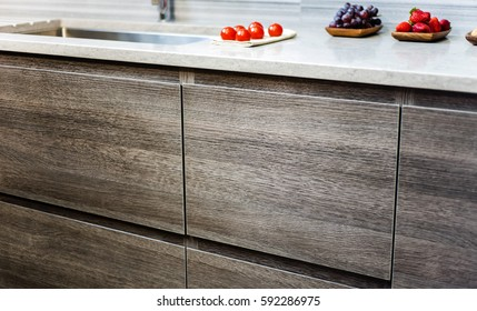 cabinets of kitchen in brown wood, granite counter over with fruits