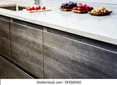 cabinets of wood, granite counter with fresh fruits on it