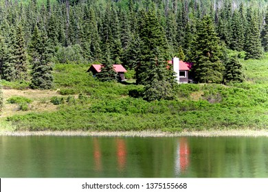 Cabins hidden by trees near a lake