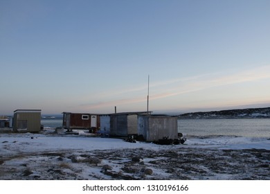 Cabins and an Inuit sled covered with slight snow near the community of Rankin Inlet, Nunavut, Canada