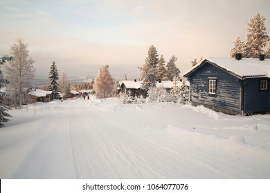 Cabins and a road in the winter and snowy landscape in the Swedish forest