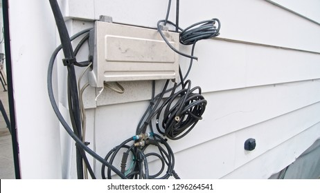 A cable box with tangled wires attached on the siding of a residential building in horizontal image format.