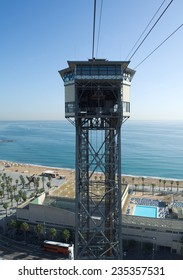 cable car is approaching pillar hosting the entrance station inside the area of port of barcelona, spain.