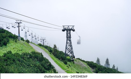 Cable car disappearing into the fog on a green mountain with grass and trees. Power towers standing on the slope and a path in the foreground leading to no where.