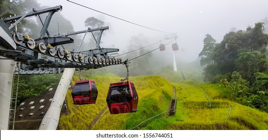 cable car at genting highlands, malaysia in a foggy weather with green grass visible from inside cable car