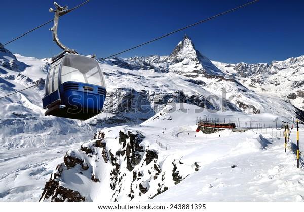 Cable car with ski slope in mountains near Zermatt, Switzerland. Swiss Alps with Matterhorn (peak Cervino),  train and ski lift.