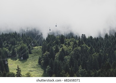 Cable cars lifting into the fog of the summit clouds
