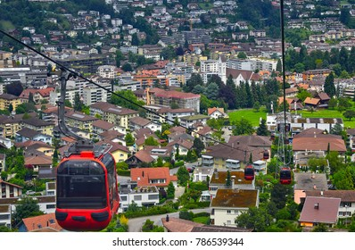 Cable cars plying on Mount Pilatus rope way against a backdrop of Lucerne city